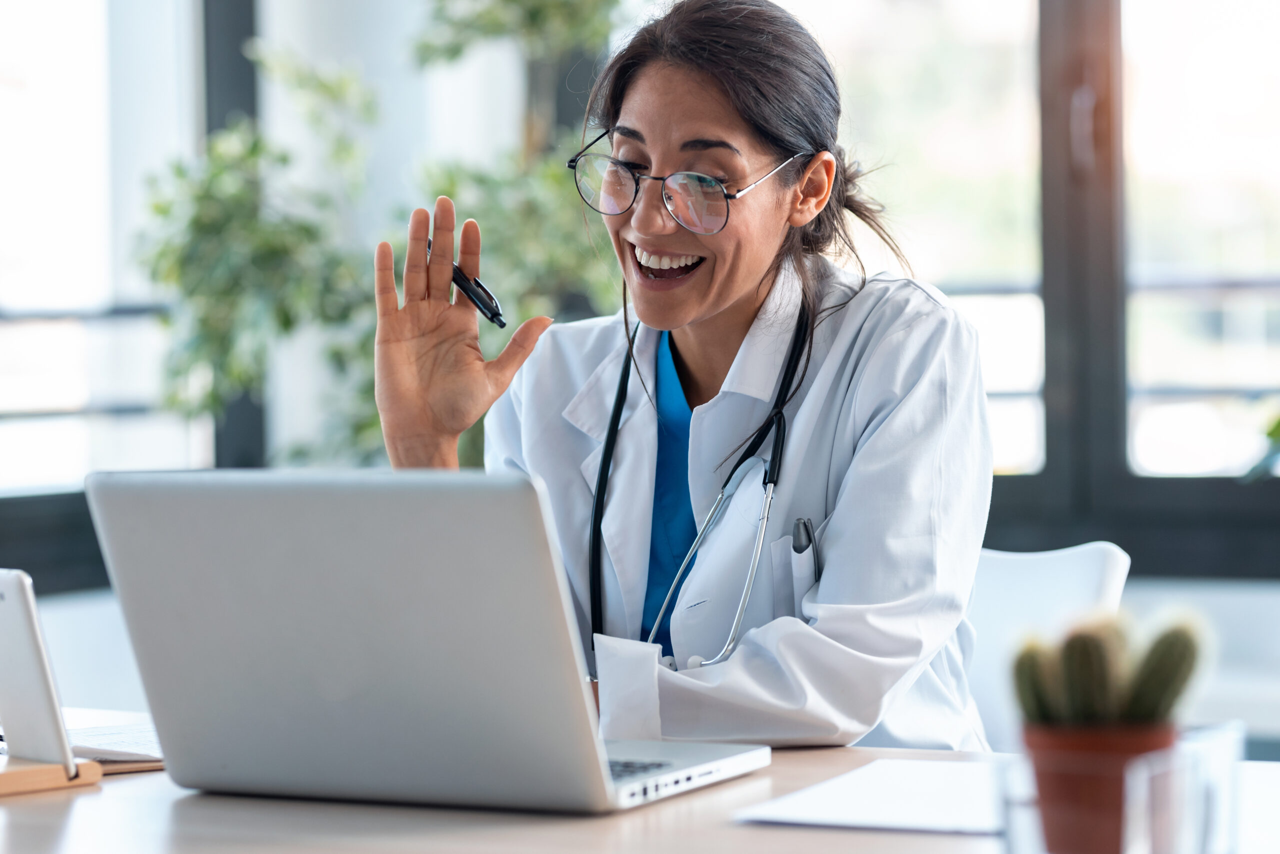 Ways healthcare professionals can improve telehealth appointments for patients, female doctor waving and smiling during telehealth appointment
